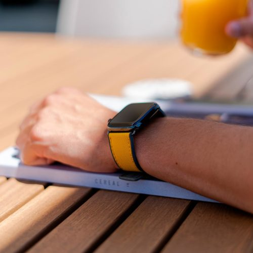 Submarine-Apple-watch-yellow-rubber-band-on-top-of-a-designer-magazine